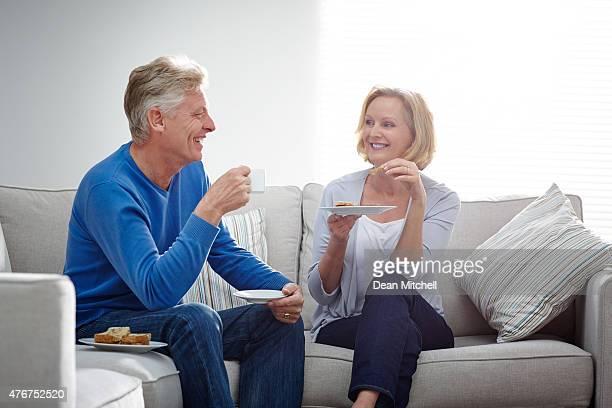 Älteres Paar entspannenden auf sofa mit Abendessen