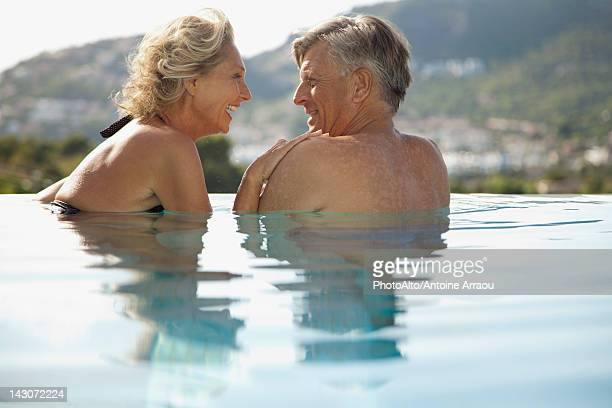 Mature couple relaxing together in pool, rear view