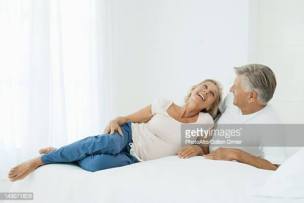 Mature couple relaxing together on bed