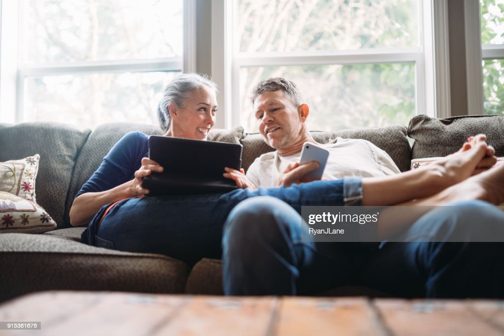 Mature Couple Relaxing with Tablet and Smartphone : Stock Photo