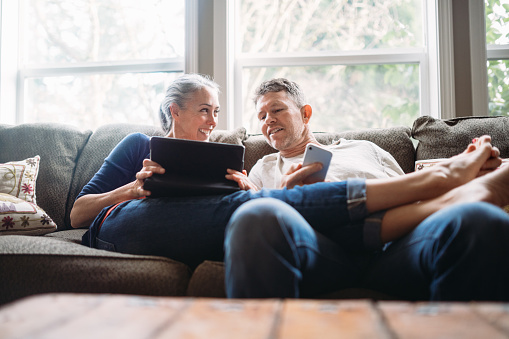 Mature Couple Relaxing with Tablet and Smartphone 915361676