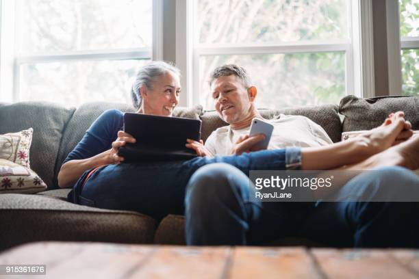 mature couple relaxing with tablet and smartphone - sofa stock pictures, royalty-free photos & images