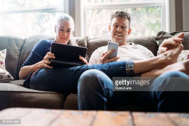mature couple relaxing with tablet and smartphone - husband massage wife stock photos and pictures