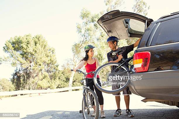 Mature couple removing bicycles from car boot in park