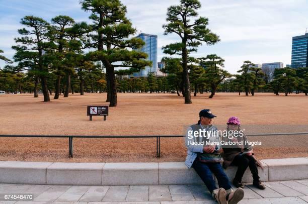 Mature couple resting in Kokyo Gaien garden