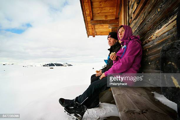 mature couple resting on bench in snow covered winter landscape