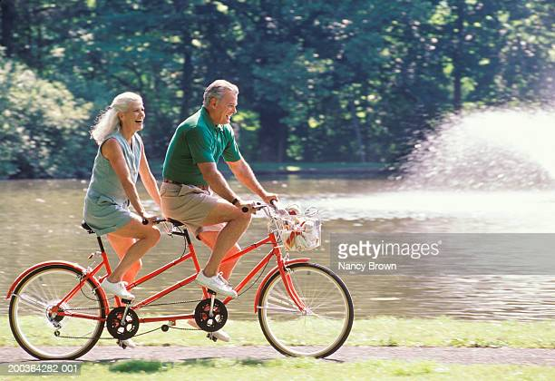 Mature couple riding bicycle for two, side view