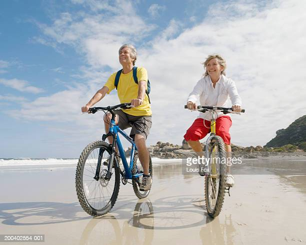 Mature couple riding bicycles on beach, smiling, low angle view