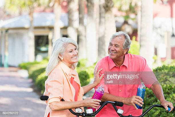 Mature couple riding bicycles on vacation