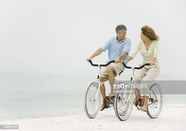 Mature couple riding bikes on beach