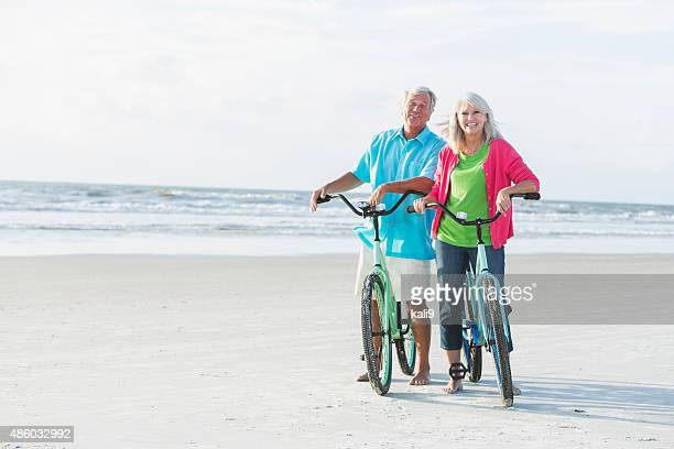 Mature couple riding bikes on the beach