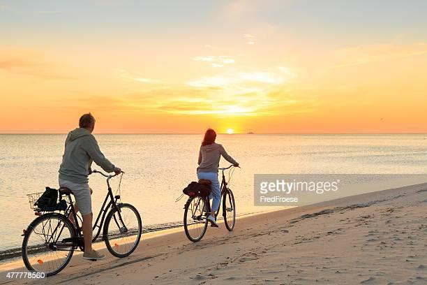 matura coppia biciclette equitazione all'aperto sulla spiaggia al tramonto - crepuscolo foto e immagini stock