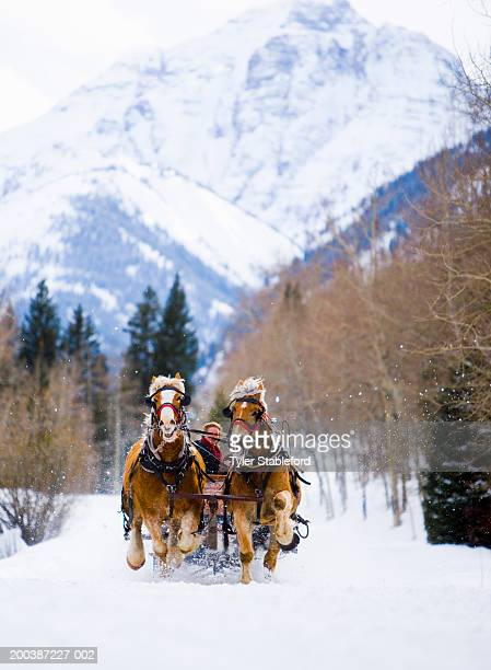 Mature couple riding horse-drawn sleigh on snow, mountains behind
