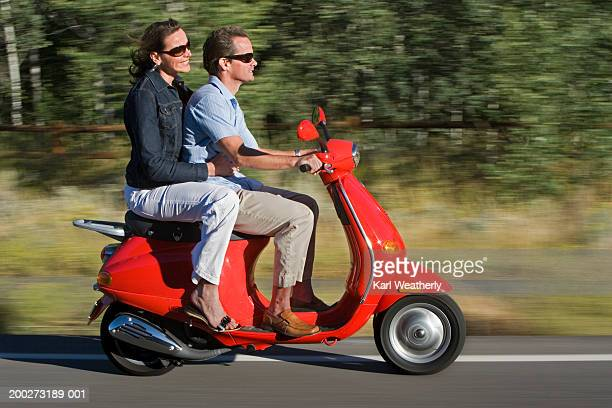 mature couple riding motor scooter in country, side view - のりものに乗る ストックフォトと画像