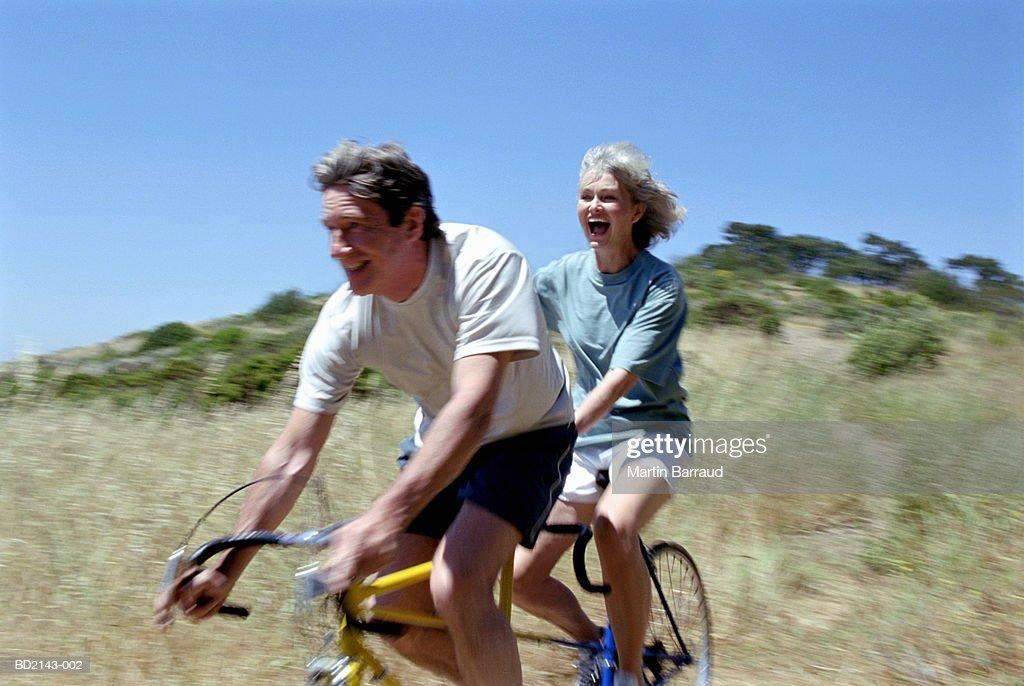Mature couple riding tandem, smiling (blurred motion) : Bildbanksbilder