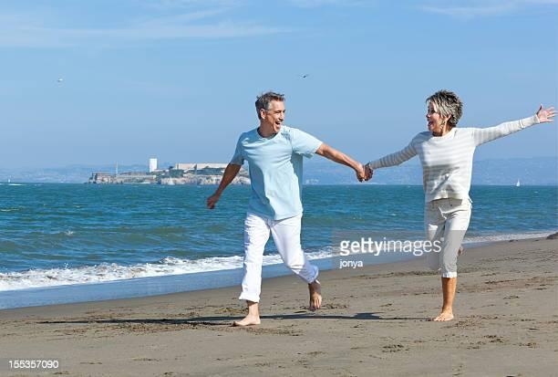 mature couple running along the beach