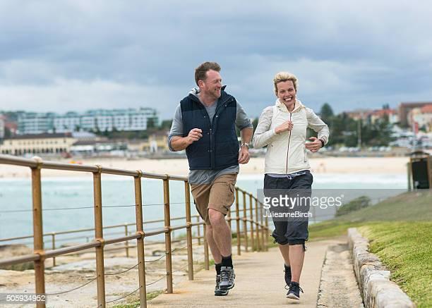 Mature couple running, Bondi Beach