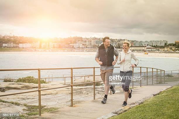 Mature couple running in Bondi Beach at sunset