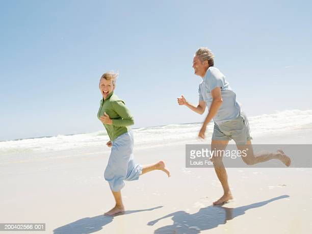 mature couple running on beach, smiling, side view - 日常から抜け出す ストックフォトと画像