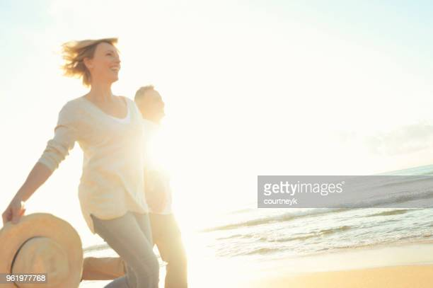 Mature couple running on the beach at sunset or sunrise.