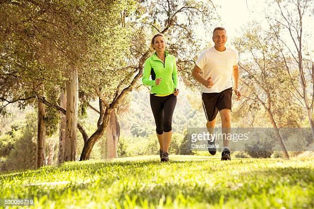 Mature couple running through park