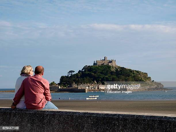 Mature couple sat on the seawall overlooking St Michael's Mount Marazion Cornwall UK
