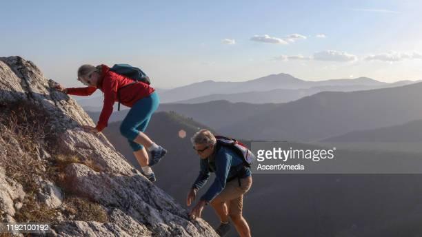 成熟したカップルは山の尾根をスクランブル - スクランブリング ストックフォトと画像