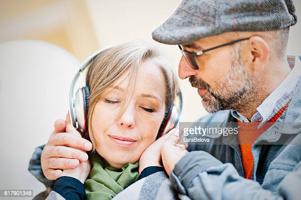 mature couple share a music by headphones - real wife sharing stock photos and pictures