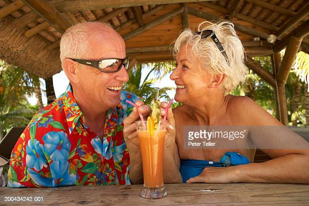 Mature couple sharing tropical cocktail, smiling