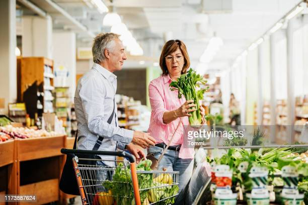 mature couple shopping for groceries at local supermarket - produce aisle stock pictures, royalty-free photos & images