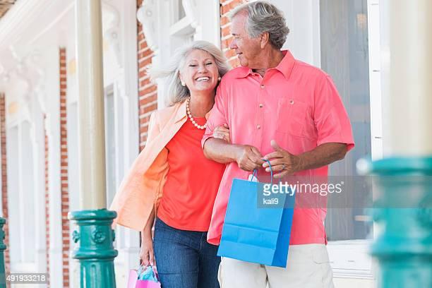 Mature couple shopping, walking outside building