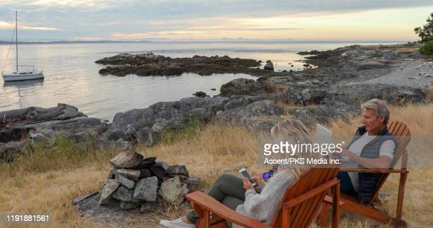 mature couple sit in wooden chairs on a knoll above the ocean - early retirement stock pictures, royalty-free photos & images