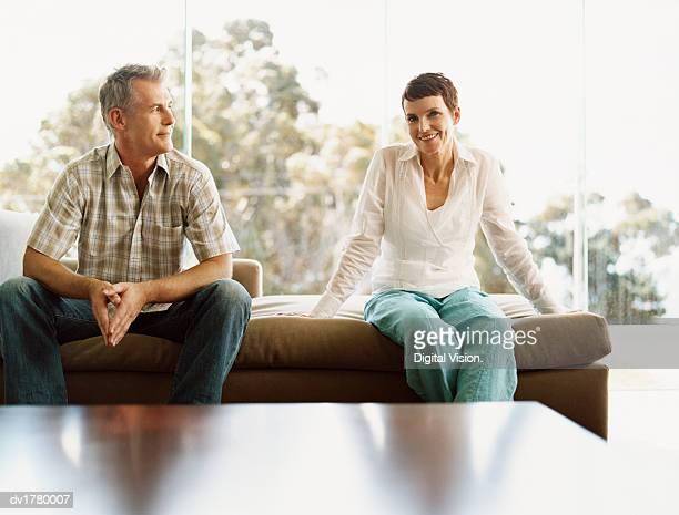 mature couple sit side-by-side on a chaise-lounge in front of a window - côte à côte photos et images de collection