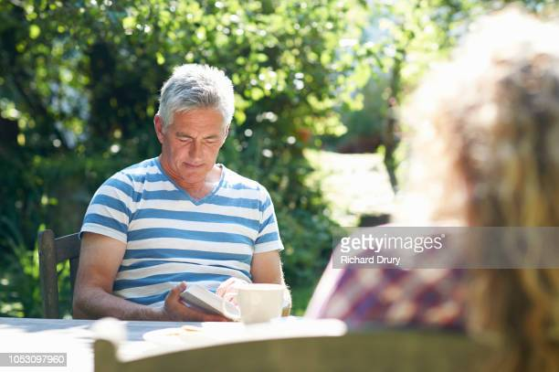 Mature couple sitting at a table in their garden