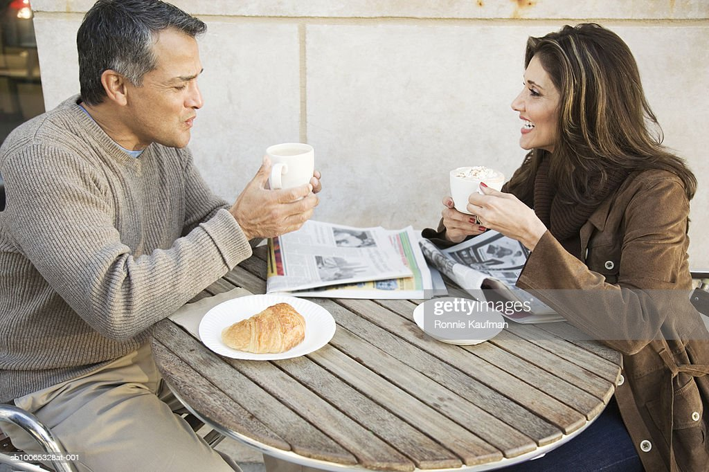 Mature couple sitting at outdoor cafe, smiling : Foto stock
