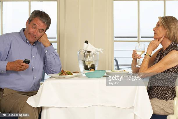 Mature couple sitting at table in restaurant, man using mobile phone
