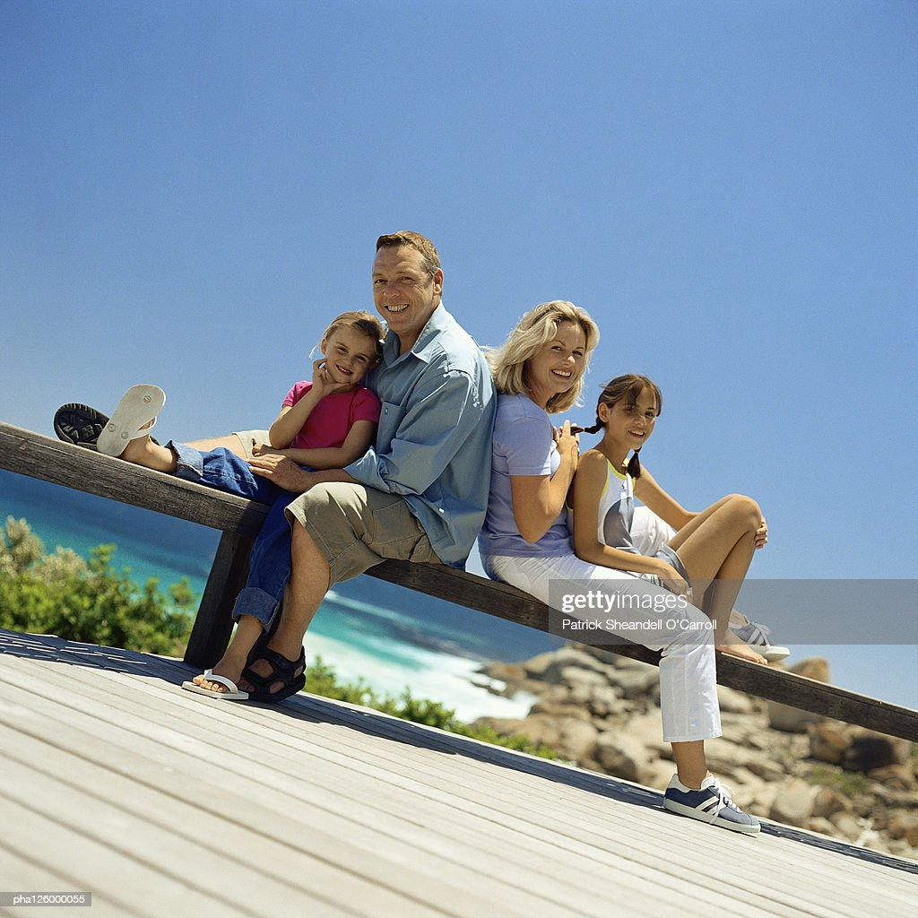 Mature couple sitting back to back with children, outside : Stockfoto