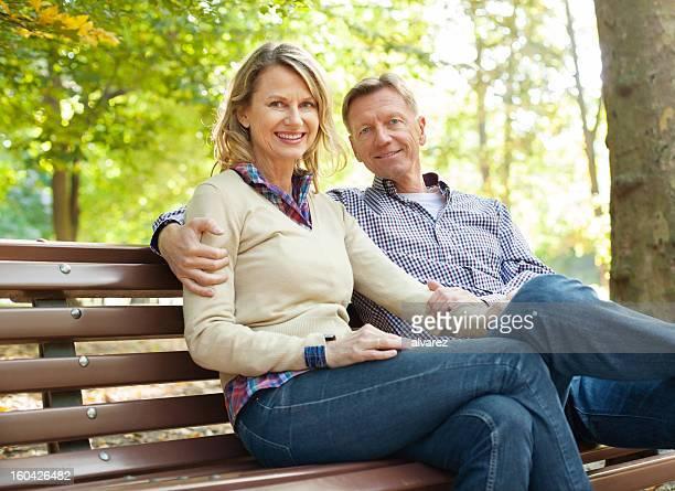 Coppia matura seduto in un parco in autunno