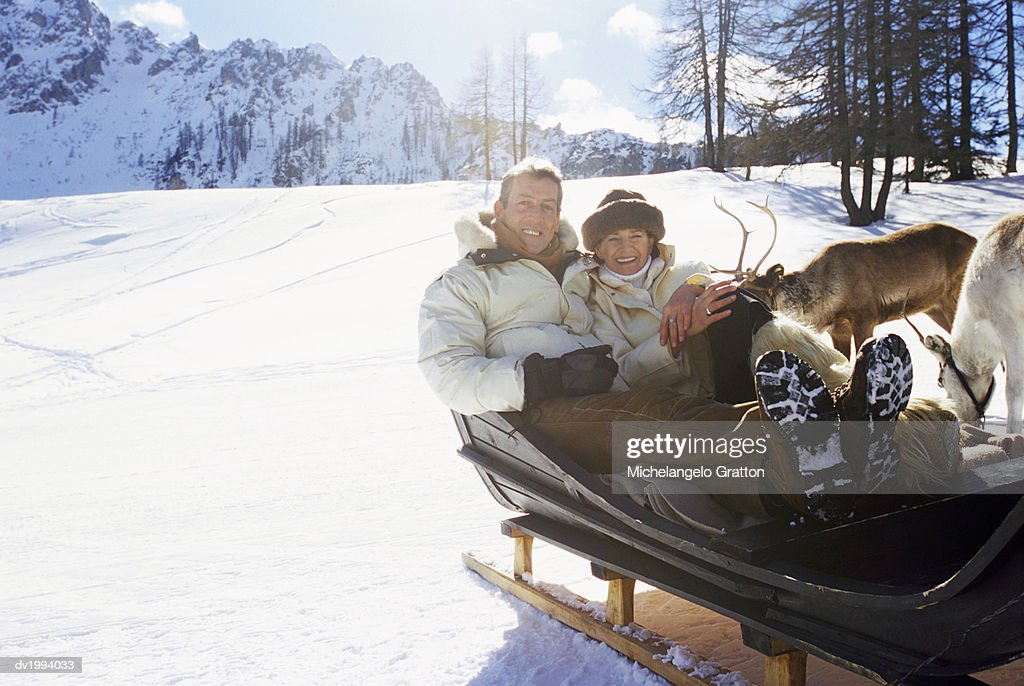 Mature Couple Sitting in a Sled : Stock Photo