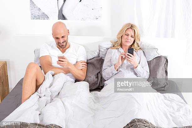 Mature couple sitting in bed using smartphones