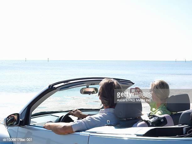 mature couple sitting in car, taking photograph - florida keys photos et images de collection