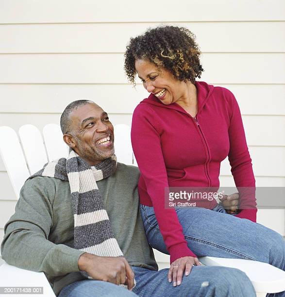 Mature couple sitting in chair in backyard, laughing