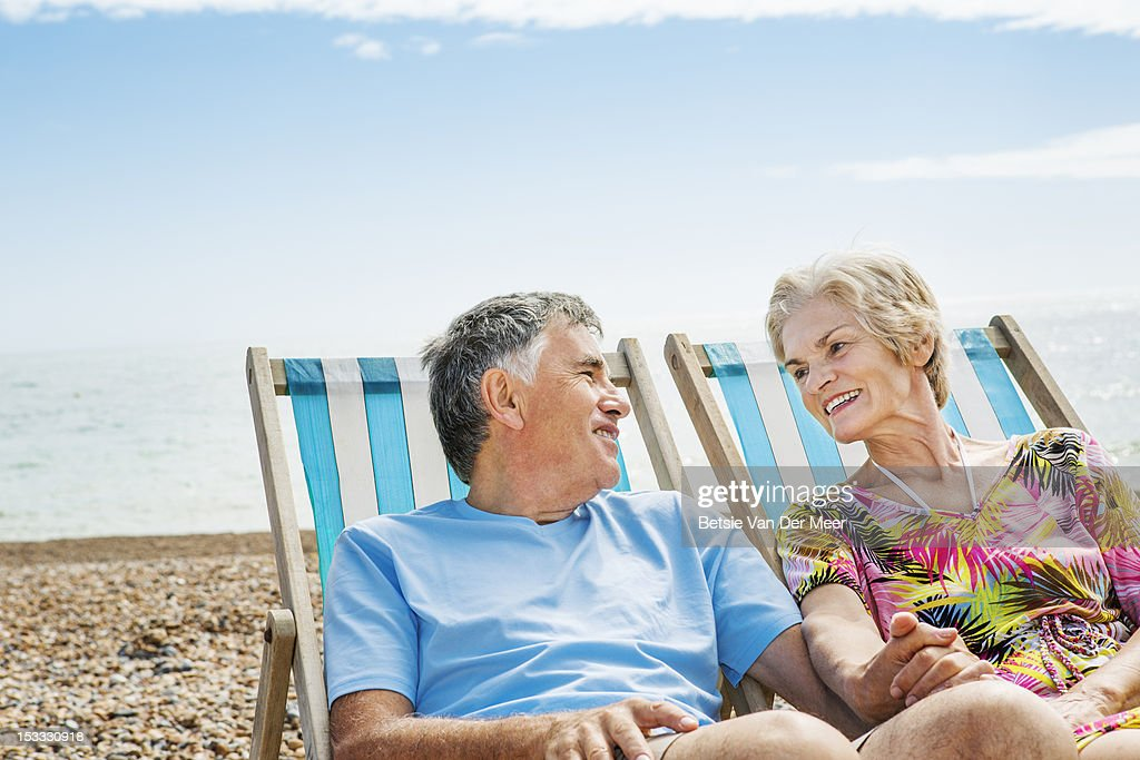mature couple sitting in deckchairs on beach. : Stock-Foto