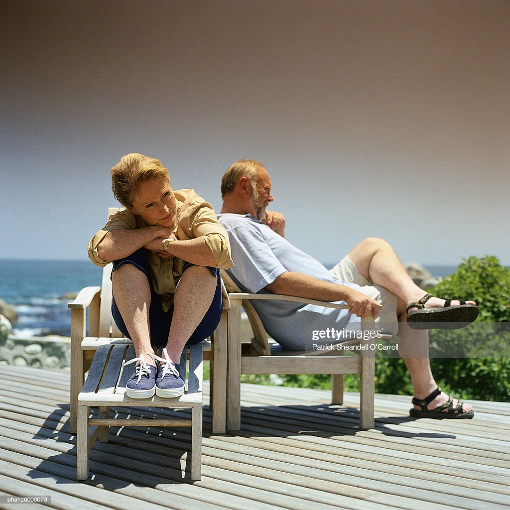 Mature couple sitting in deckchairs outside : Stockfoto