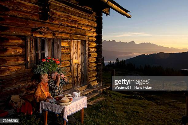 'Mature couple sitting in front of alpine hut, watching sunset'