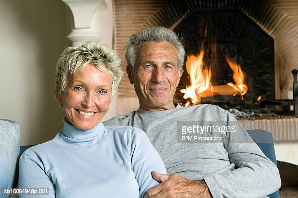 Mature couple sitting in front of fireplace, portrait