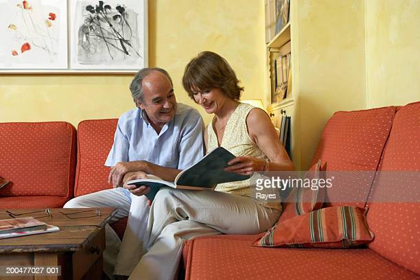 Mature couple sitting in living room looking at book, smiling
