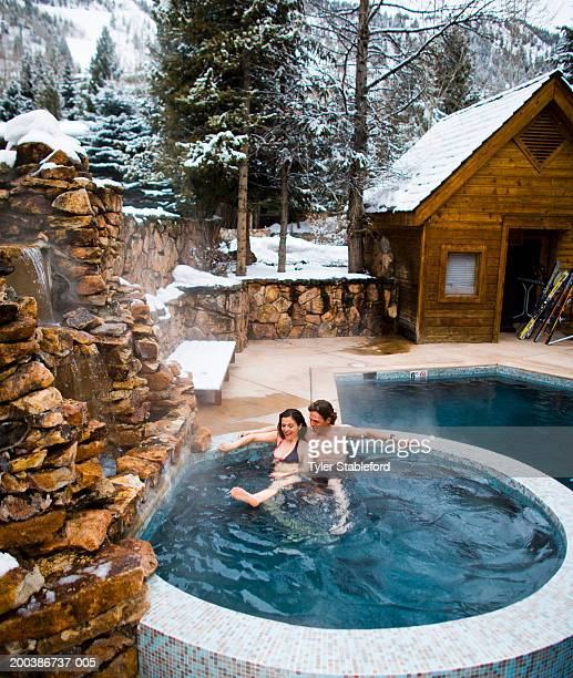 mature couple, sitting in outdoor hot tub, relaxing, elevated view - colorado stock pictures, royalty-free photos & images
