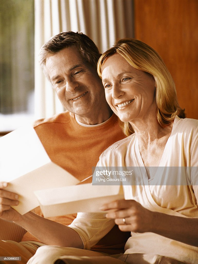 Mature Couple Sitting Indoors Together Reading a Letter : Stock Photo