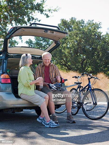 Mature couple sitting on back of car